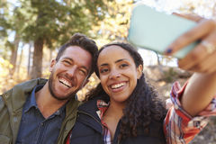Laughing mixed race couple taking a selfie in a forest Stock Image