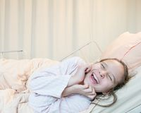 Laughing mixed race tween girl in hospital bed Royalty Free Stock Photo