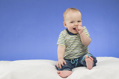 Laughing 8-month-old baby boy, sitting on the white blanket , studio shot, isolated on blue background Royalty Free Stock Image