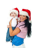 Laughing mother and baby boy with Santa hats Royalty Free Stock Photo