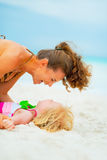 Laughing mother and baby girl playing on beach Stock Photo