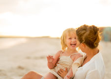 Laughing mother and baby girl sitting on beach Stock Photos