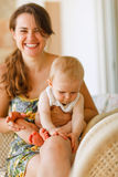 Laughing mother with baby sitting on knees Royalty Free Stock Photo