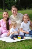 Laughing mother and children sits on grass Royalty Free Stock Photos