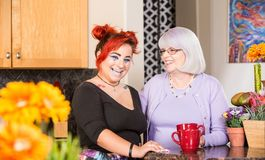 Laughing Mother and Daughter in Kitchen. Mother and daughter stand in kitchen laughing Royalty Free Stock Photography