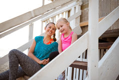 Laughing mother and daughter sitting on beach house steps Royalty Free Stock Photo