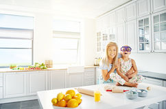 Laughing mother and daughter together in kitchen Royalty Free Stock Photos