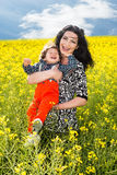 Laughing mother and son in canola field Royalty Free Stock Image
