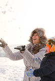 Laughing mother and son tossing snow in the air Stock Photo