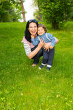 Laughing mother and toddler boy in grass Royalty Free Stock Photo