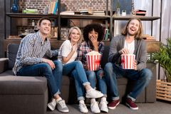 Laughing multicultural friends watching movie on sofa. With popcorn stock photo