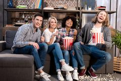 Laughing multicultural friends watching tv on sofa. With popcorn royalty free stock images