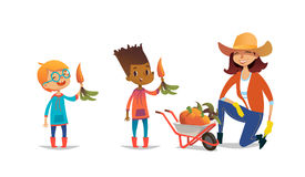 Laughing multiracial children holding carrots and female agricultural worker dressed in rubber boots and straw hat. Standing on one knee beside wheelbarrow full vector illustration
