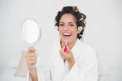 Laughing natural brunette applying lip gloss Stock Photo