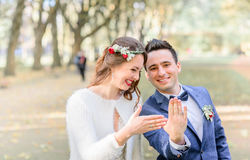Laughing newlyweds show wedding rings on their hands.  royalty free stock image