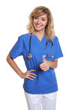 Laughing nurse showing thumb up Stock Photo
