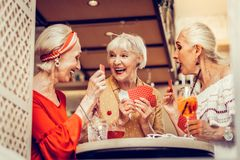 Laughing old ladies being extremely gambling while playing cards stock image