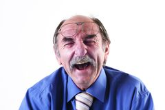 Laughing old man. A senior in a blue shirt and tie, puts his glasses on his forehead as he laughs loudly Royalty Free Stock Photos