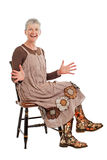 Laughing older woman sits sideways hands open Stock Images