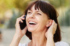 Laughing older woman talking on smart phone outside. Close up portrait of laughing older woman talking on smart phone outside Stock Images