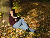 Laughing out loud. Woman reading a book and laughing out loud while relaxing under a tree amidst autumn leaves Royalty Free Stock Photo