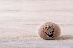 Laughing out loud emoticon. Stone face on white wood background with free space for your text Royalty Free Stock Photo