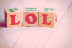 Laughing out loud. LOL sign. Wooden blocks on a white wooden background. Filtered image Stock Photo