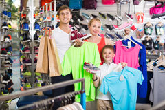 Laughing parents with boy in sport store. Laughing parents with boy in school age shopping clothing in sport store Royalty Free Stock Photography