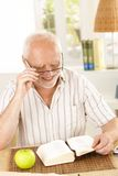 Laughing pensioner reading book. Sitting at table at home Royalty Free Stock Photo