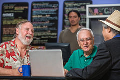Laughing People in Cafe with Laptop. Laughing people in a coffee house with laptop Stock Photo