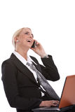 Laughing on the phone. Businesswoman sitting and working on her laptop while laughing on the phone Stock Photography