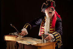 Laughing pirate with treasure map. Colorful happy old pirate captain in 18th century style costume, seated with a torn treasure map spread out on wooden desk royalty free stock photography