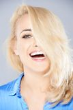 Laughing playful blond hiding behind her hair royalty free stock image
