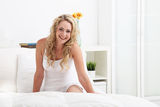 Laughing playful woman on her bed Stock Images