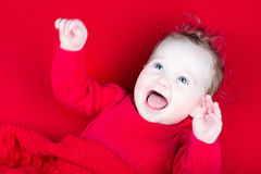 Laughing playing baby girl under a red blanket. Laughing little playing baby girl under a red blanket Royalty Free Stock Images