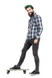 Laughing positive hipster with smiley piercing standing on skateboard side view. Royalty Free Stock Photo