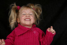 Laughing Pre-schooler. A happy little girl laughing in a pink sweater Stock Images