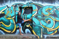 Laughing pregnant girl standing in door with abstract street art