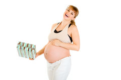Laughing pregnant woman holding gift for her baby Stock Images