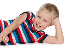 Laughing preschool boy on the white. A laughing preschool boy is lying on the white background Royalty Free Stock Photography