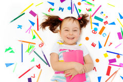 Laughing preschool girl holding pink book Stock Images