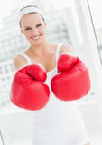 Laughing pretty sportswoman showing her boxing gloves Royalty Free Stock Photo