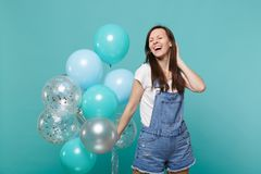 Laughing pretty young woman in denim clothes keeping eyes closed celebrating, holding colorful air balloons isolated on. Blue turquoise wall background stock photo