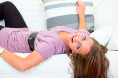 Laughing pretty young woman lying on white couch Stock Photo