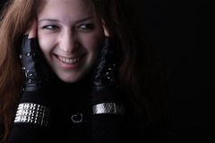 Laughing punk rock girl portrait. Young woman holding her head and smiling on black, studio Stock Photo