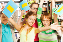 Laughing pupils with exercise books up in library royalty free stock image