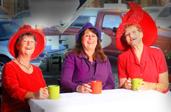 Laughing Red Hat Ladies. Three pretty laughing Red Hat Ladies sitting in a cafe having coffee. Shallow depth of field stock photos