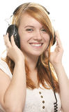 Laughing redhead girl with headphones listening to Stock Image