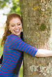 Laughing redhead hugging a tree Stock Photos