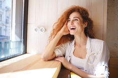 Laughing redhead young lady sitting in cafe. Stock Photo